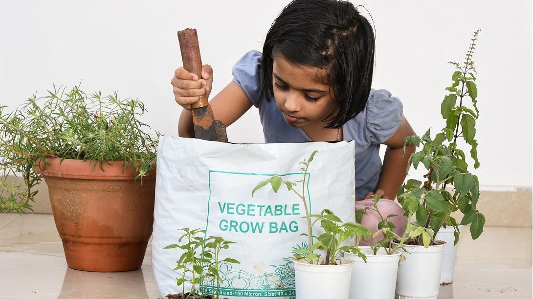 Une jeune écolière aide à la construction d'un jardin végétal dans son école en Inde.